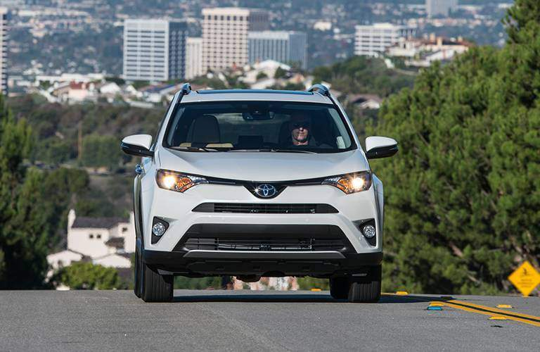 2016 Toyota RAV4 driving up a hill with a large city in the background
