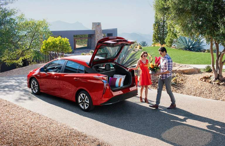 2016 Toyota Prius parked in a driveway with the hatchback open and cargo space full of pillows and the owners standing next to the vehicle with a plant