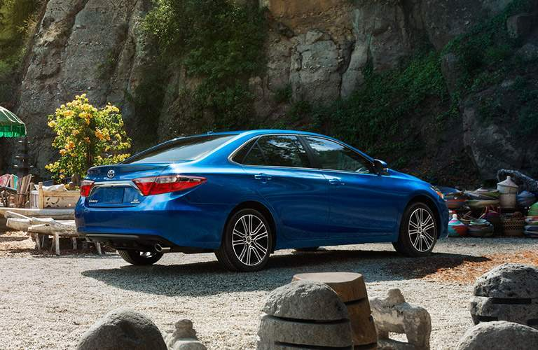 2016 Toyota Camry in blue parked on a rocky beach
