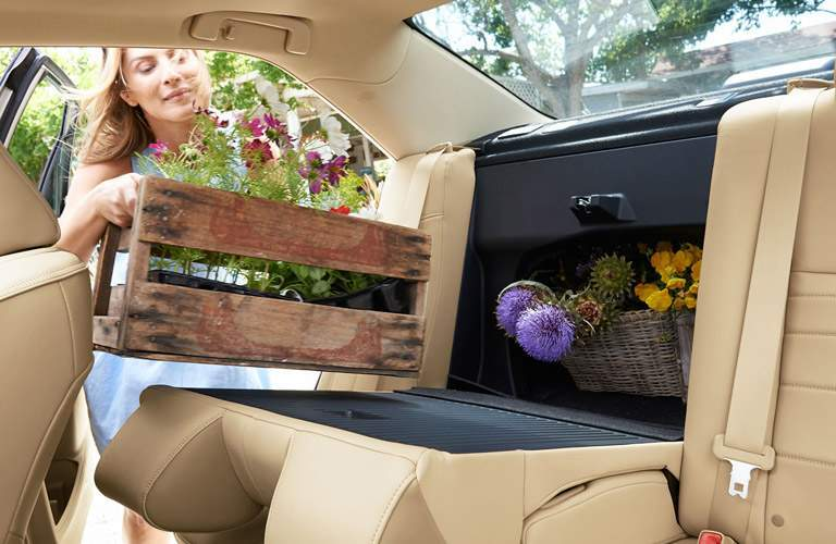 woman setting flowers in the rear seat of the 2016 Toyota Camry