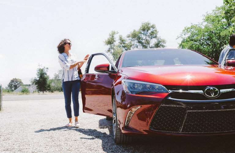 Passenger closing the door of a red 2016 Toyota Camry
