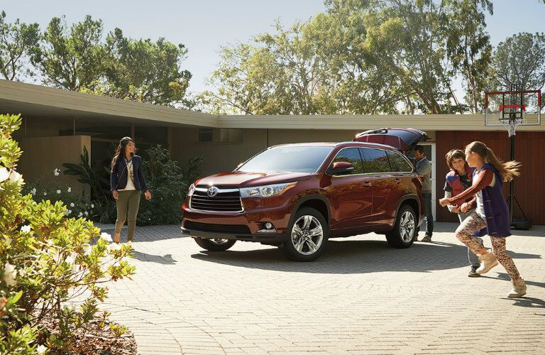 2016 Toyota Highlander parked in a large driveway while a family plays basketball