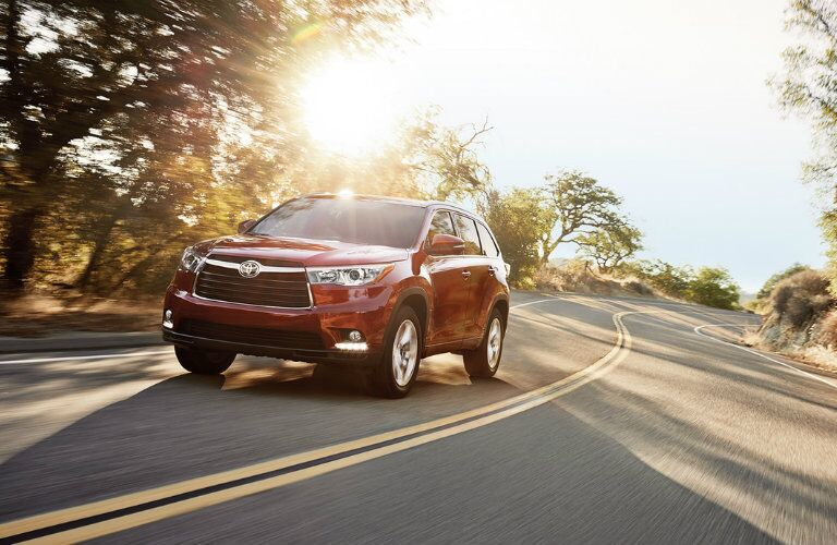 2016 Toyota Highlander in red driving down the road