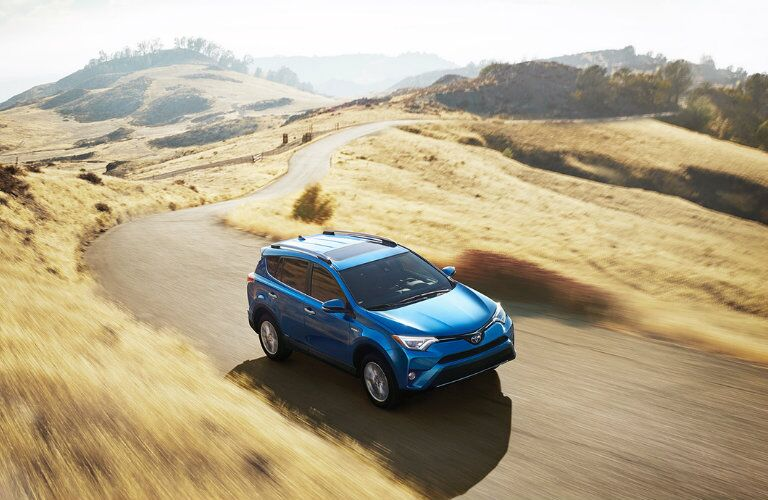 2016 Toyota RAV4 driving on a country road surrounded by tan fields