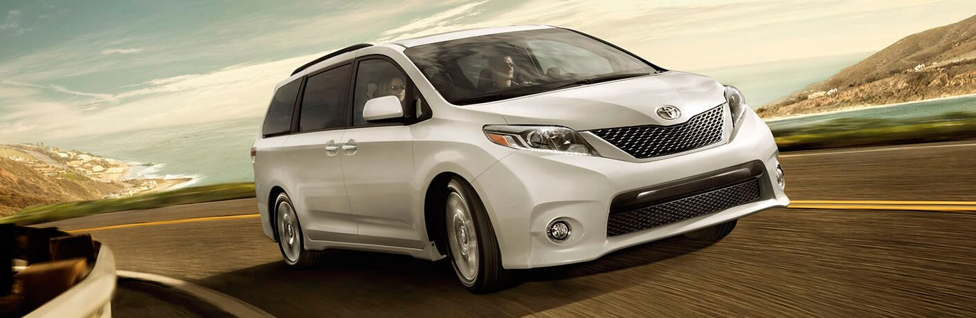2017 Toyota Sienna in white driving on a highway near the ocean