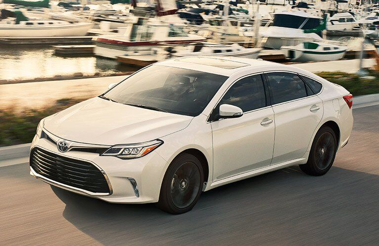 2016 Toyota Avalon in white driving next to a marina