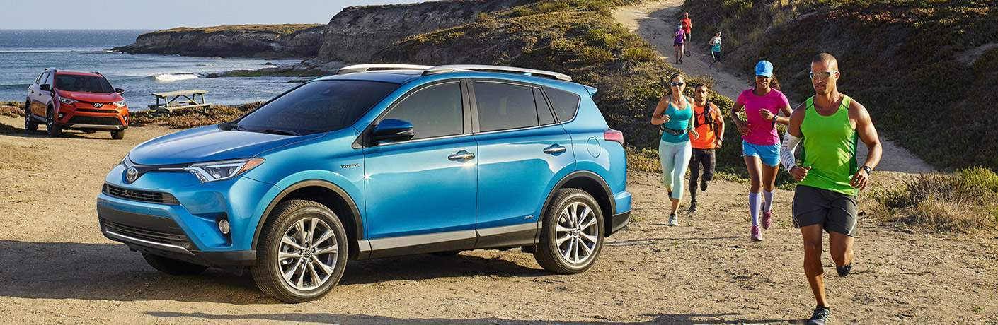 2017 Toyota RAV4 in blue parked at the beach near a bunch of runners