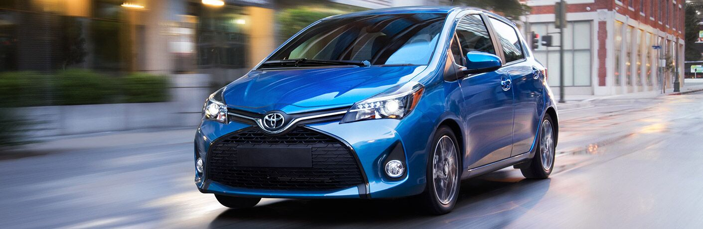 2017 Toyota Yaris model in blue driving down an empty city street