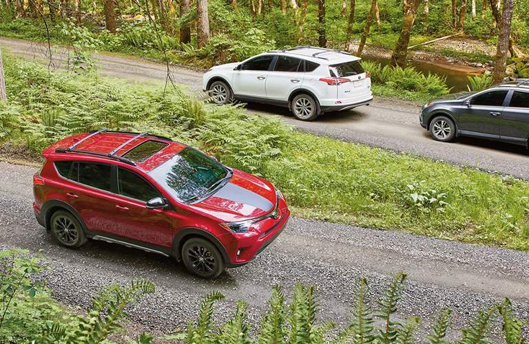 Multiple 2018 Toyota RAV4 Hybrid models driving down a gravel tree-lined road
