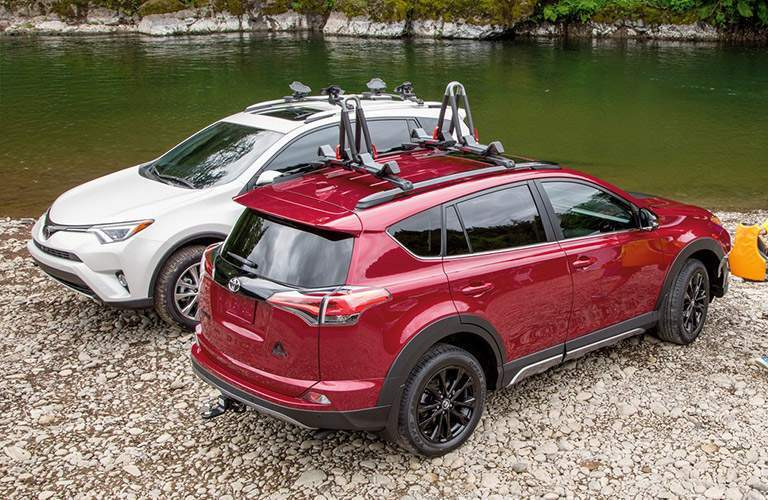 Two 2018 Toyota RAV4 Hybrid models parked in gravel at the edge of a lake