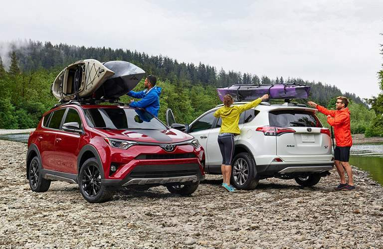 Two 2018 Toyota RAV4 Hybrid models parked on a rocky beach with kayaks on the roof rails