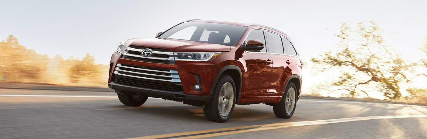 2018 Toyota Highlander Hybrid in red driving down the road