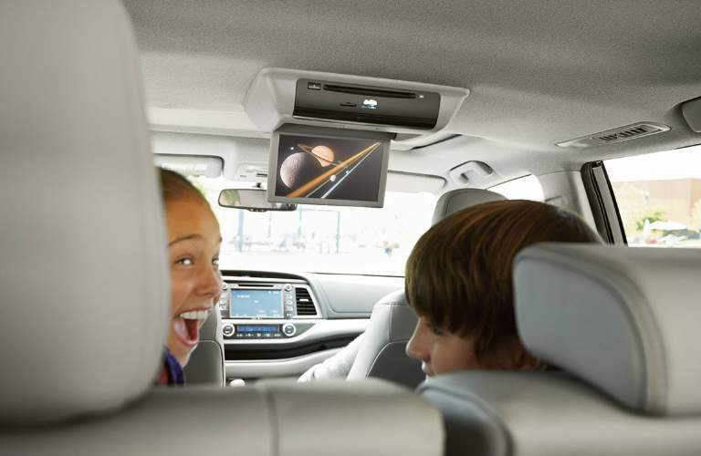 Passengers watching the rear seat entertainment display on the 2018 Toyota Highlander Hybrid
