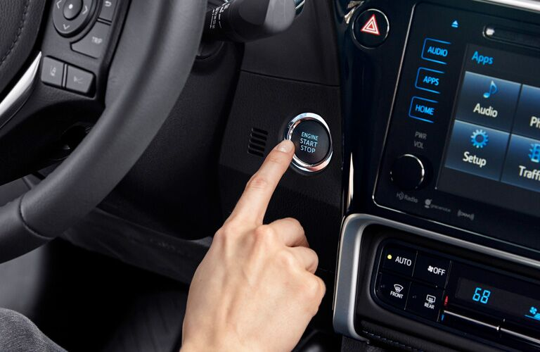 Someone pushing the push button start in the 2019 Toyota Corolla