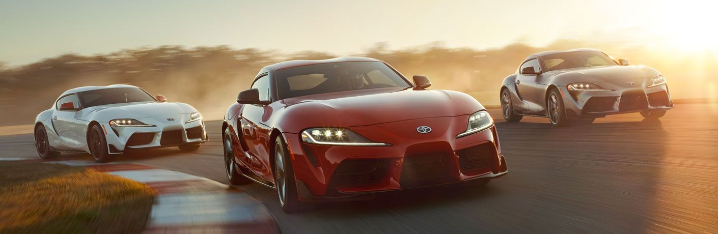Three 2020 Toyota Supra models driving on a race track at dusk