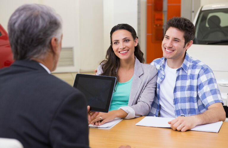couple talking at a desk with a car dealership representative