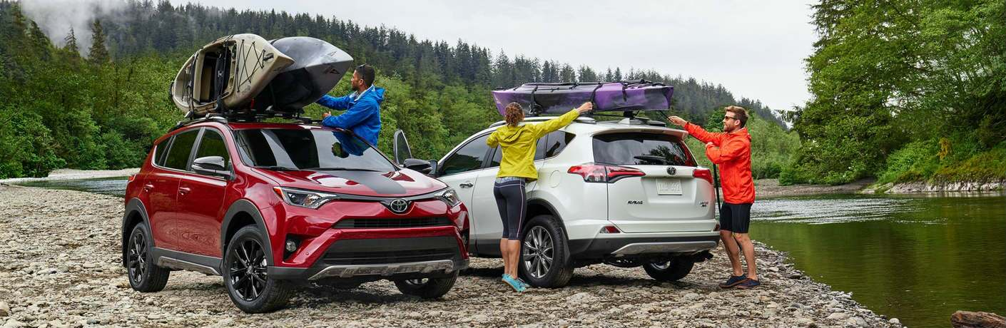Two Toyota RAV4 models with kayaks on the roof parked near a lake