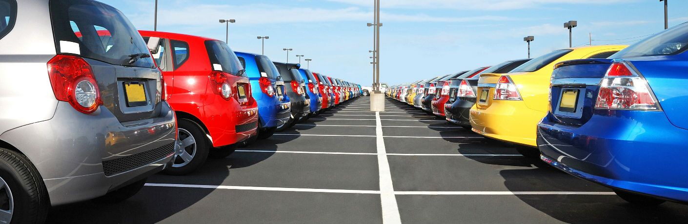 Two rows of colorful vehicles on a dealership lot