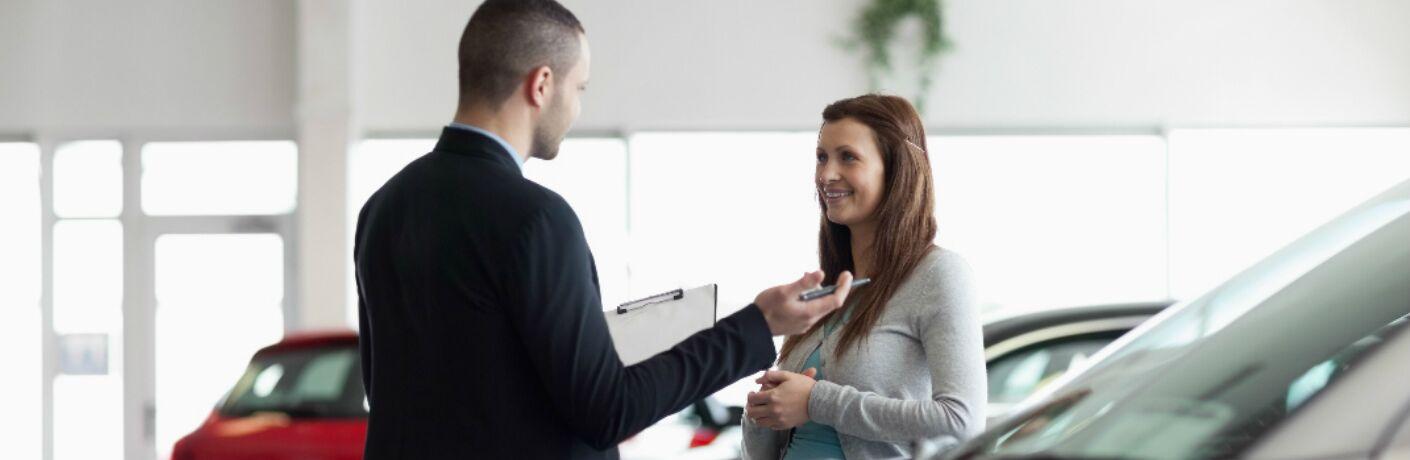 car shopper talking with a dealership representative in a showroom