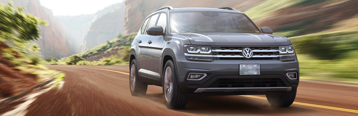 gray 2018 VW Atlas driving through wilderness road front view