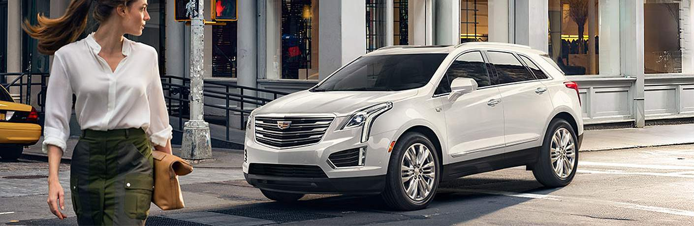 woman walking by white 2018 cadillac xt5 on city street