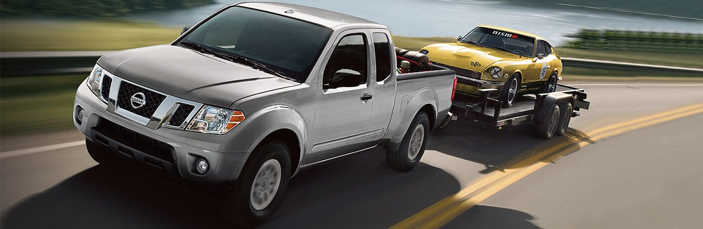 silver 2018 nissan frontier towing classic yellow sports car in trailer