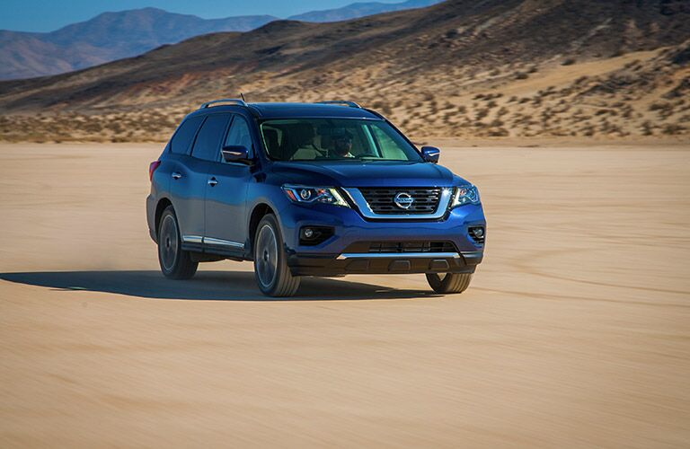 blue 2018 nissan pathfinder driving through desert