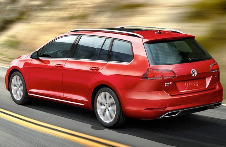 Exterior view of a red 2018 Volkswagen Golf SportWagen driving down a country road away from the camera