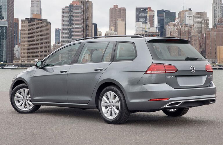 Exterior view of the rear of a gray 2018 Volkswagen Golf SportWagen parked next to a river in a major city