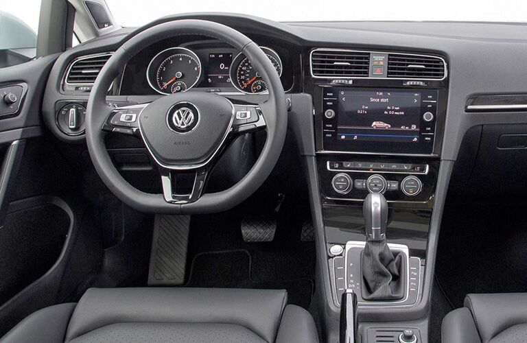 Interior view of the black steering wheel and dashboard of a 2018 Volkswagen Golf