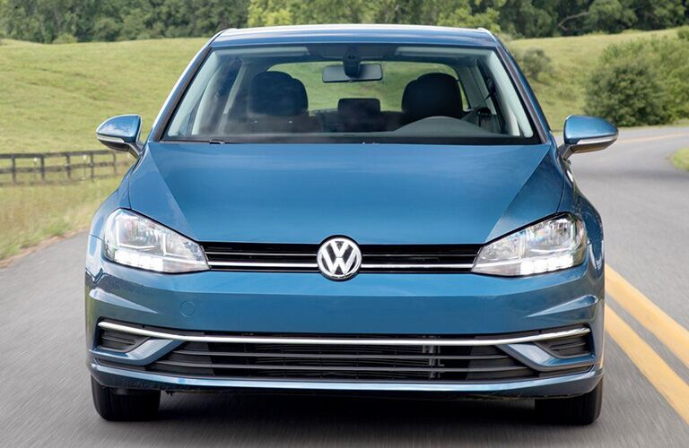 Exterior view of the front of a blue 2018 Volkswagen Golf driving down a two-lane road in the country