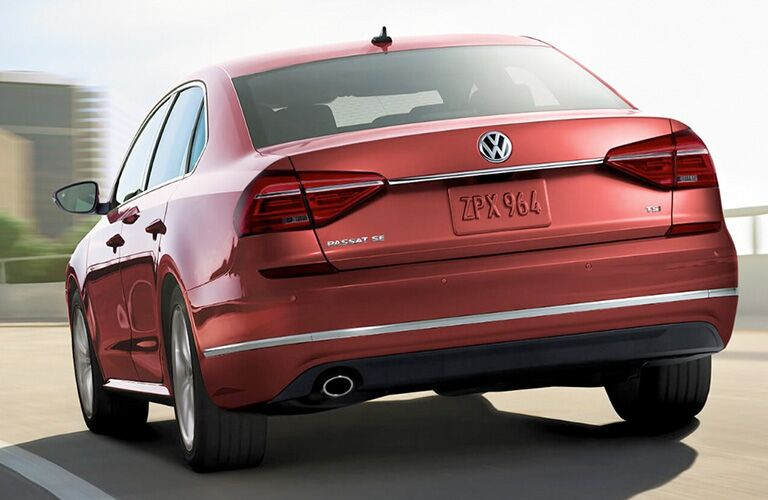Exterior view of a red 2018 Volkswagen Passat driving away from the camera on a highway