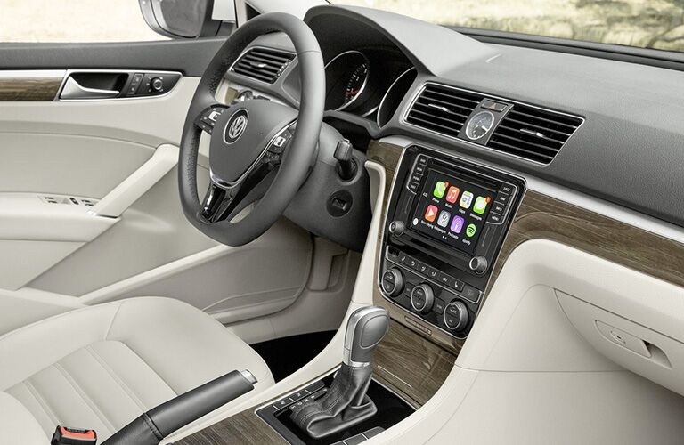 Interior view of the front tan seating, black steering wheel, and touchscreen of a 2018 Volkswagen Passat