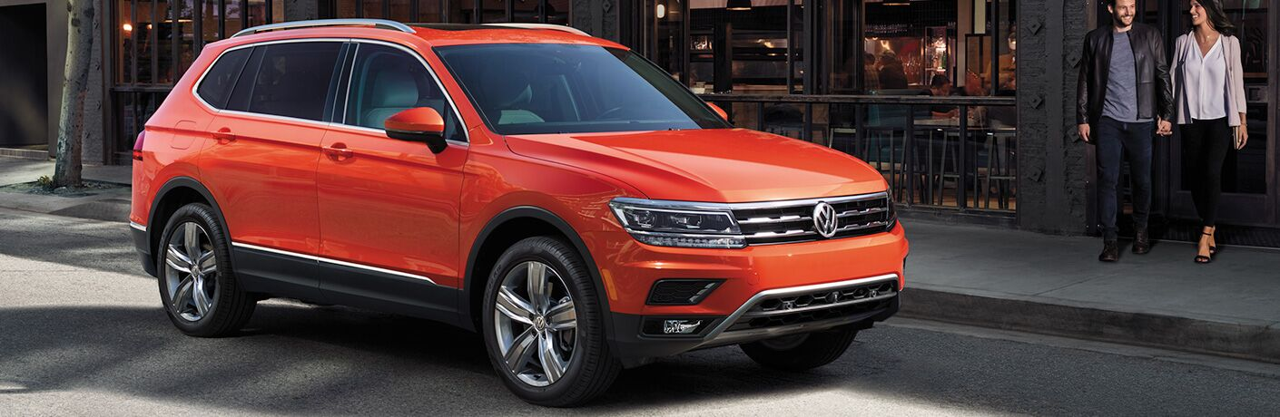 Exterior view of an orange 2018 Volkswagen Tiguan parked outside a restaurant in the city