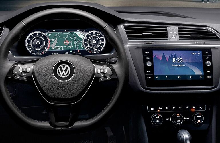 Interior view of a 2018 Volkswagen Tiguan showing closeup of steering wheel and infotainment system touchscreen
