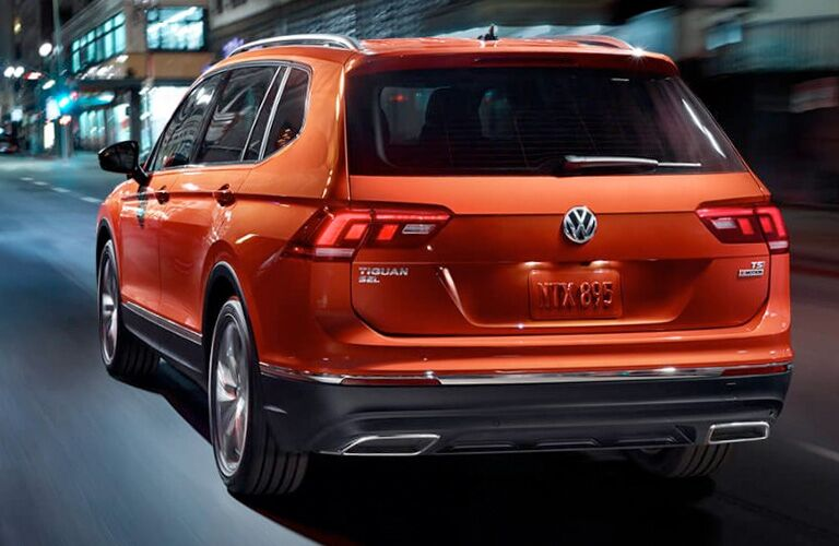 Exterior view of an orange 2018 Volkswagen Tiguan driving down a city street at night
