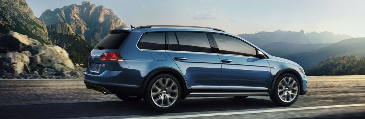 Exterior view of a light-blue 2018 Volkswagen Golf Alltrack driving down a highway with mountains in the background