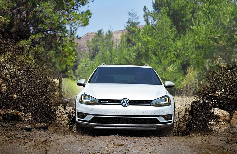 Exterior view of the front of a white 2018 Volkswagen Golf Alltrack driving through muddy terrain