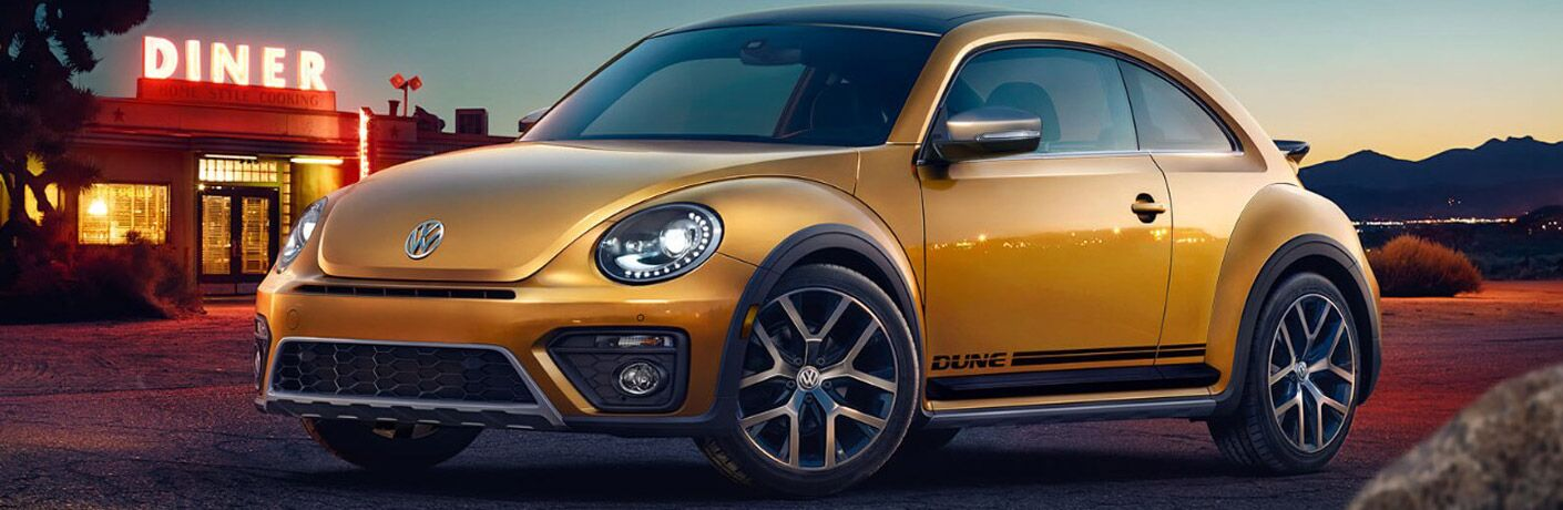 View of gold 2018 Volkswagen Beetle parked outside of a diner at sundown