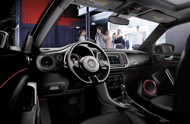 View of 2018 VW Beetle black interior with red trim highlighting the steering wheel and gear shifter