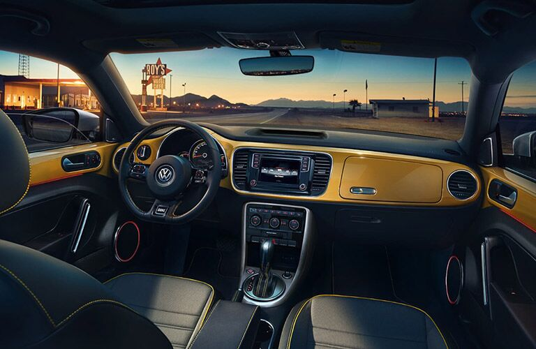 View of 2018 VW Beetle gold and black interior highlighting steering wheel and touch panel