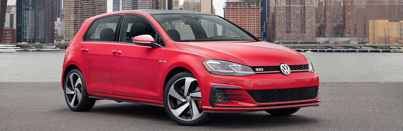 View of red 2018 Volkswagen Golf GTI parked in the city with a river and city skyline in the background