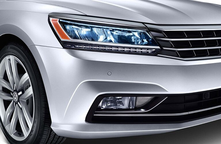 Exterior view of a silver 2018 Volkswagen Passat zoomed in on the headlight and bumper