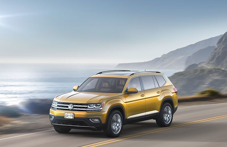 Exterior view of a gold 2018 Volkswagen Atlas driving down a coastal highway with the ocean in the background