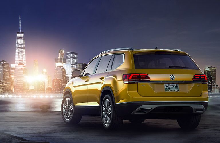 Exterior view of the rear of a gold 2018 Volkswagen Atlas parked facing a river and city skyline at night