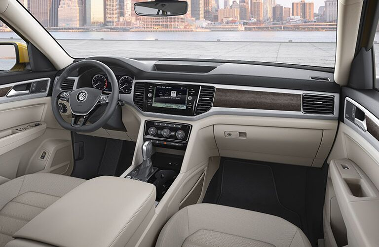 Interior view of the tan seating, black steering wheel, and infotainment touchscreen of a 2018 Volkswagen Atlas