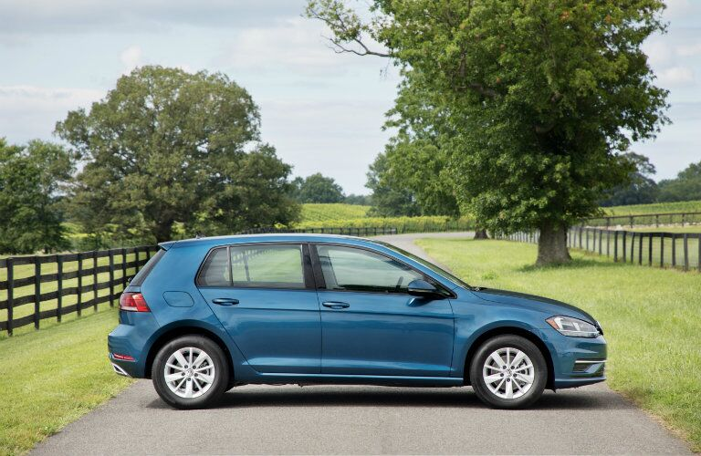 2018 Volkswagen Golf exterior side shot of teal color parked on a country road with grass, trees, and a wooden fence in the background