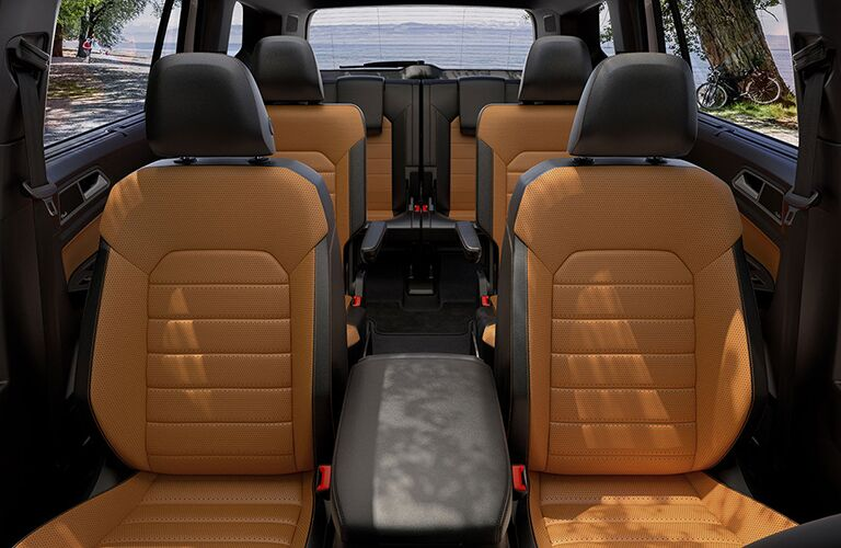 Interior view of the three rows of orange and black seating from front to back in a 2019 Volkswagen Atlas