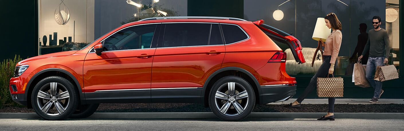 Exterior view of an orange 2019 Volkswagen Tiguan parked in the city with a woman opening the tailgate with her foot to load her shopping purchases