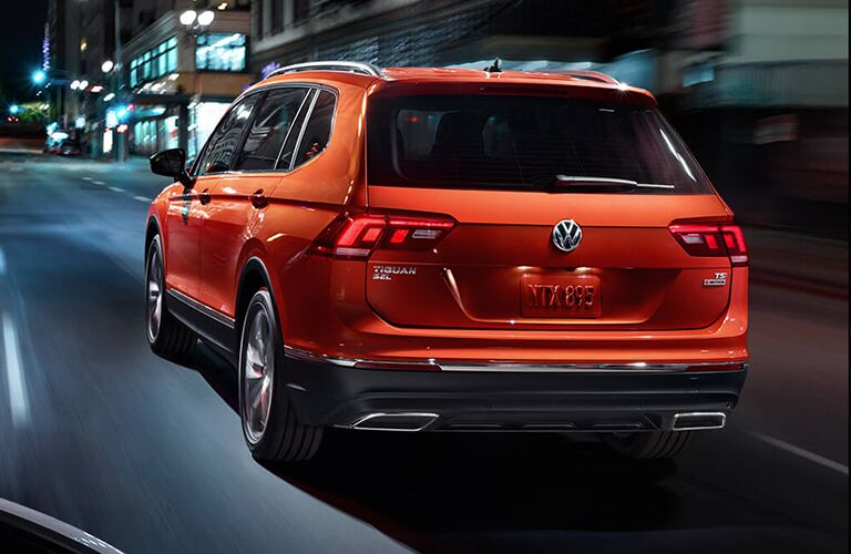 Exterior view of the rear of an orange 2019 Volkswagen Tiguan driving down a city street at night